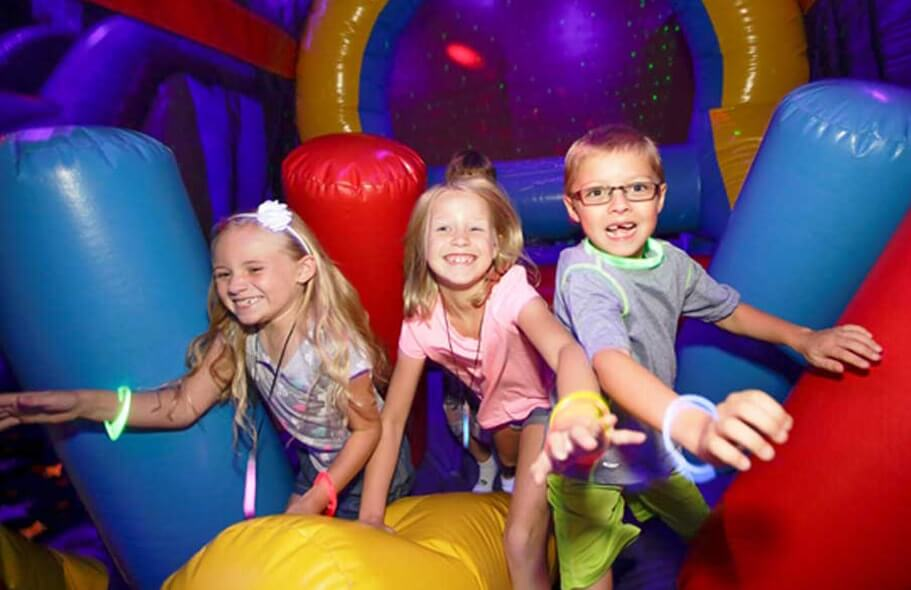 Three kids having fun bouncing in an inflatable.