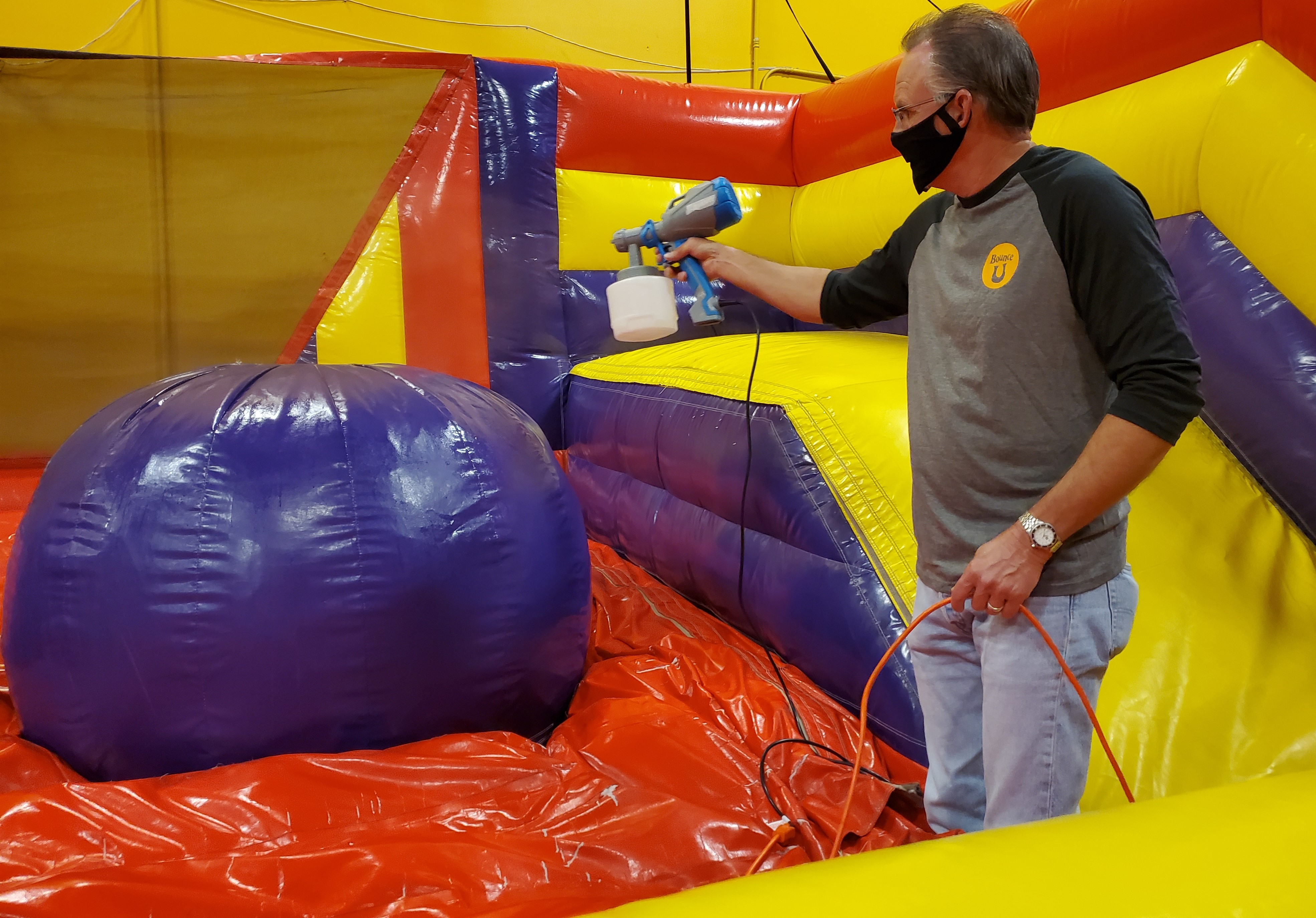 party pro at BounceU disinfecting inflatable attraction rides using a spray hand help device
