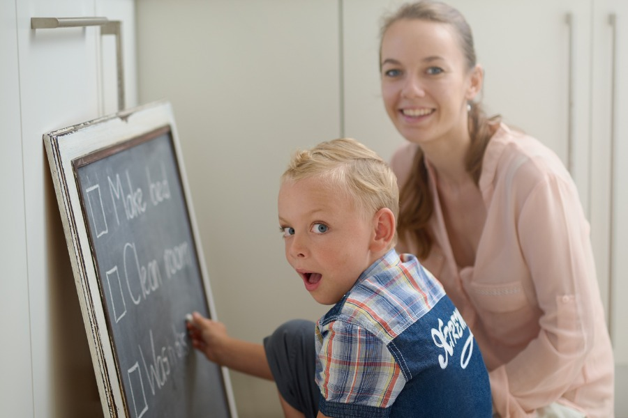 mom and son working on daily checklist schedule