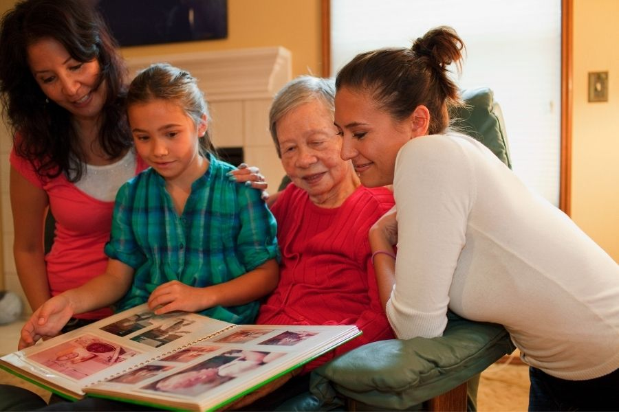 Mom with daughter and grandmother looking at family photos having Screen Free family time