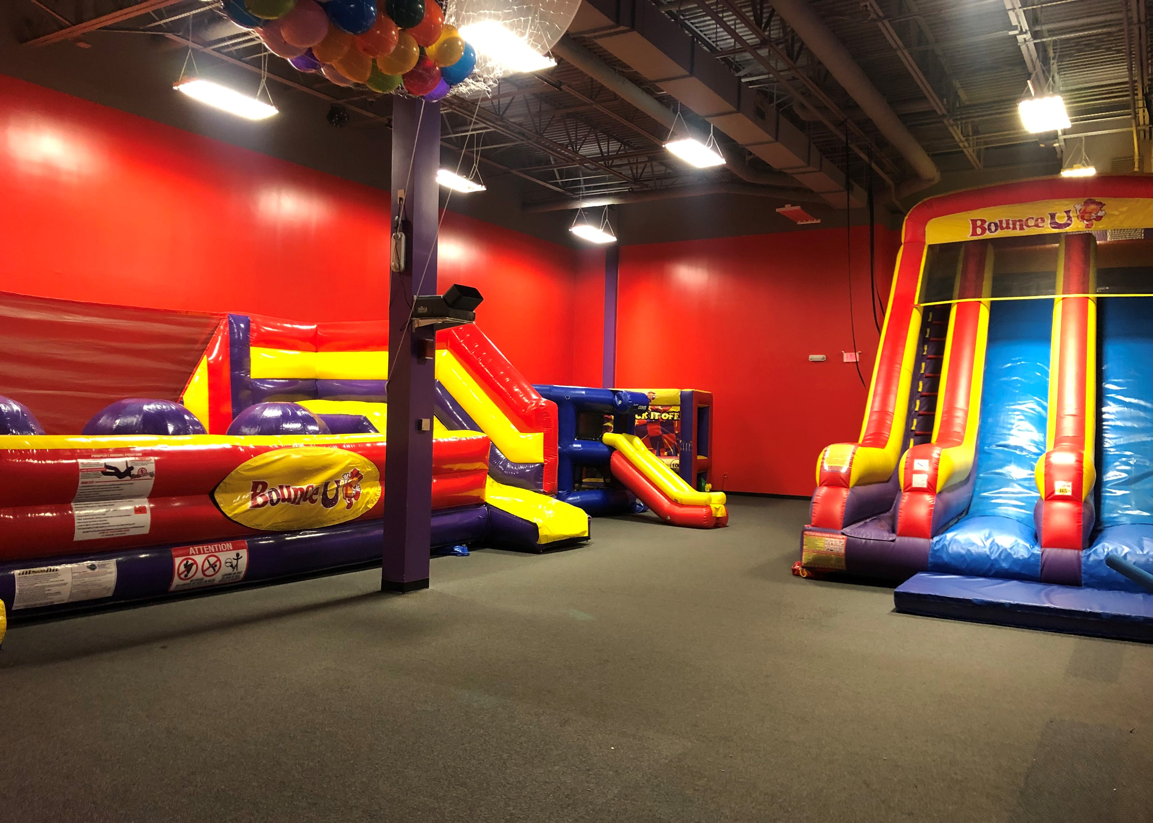 BounceU birthday party arena space with two large inflatable rides and two small inflatable games.
