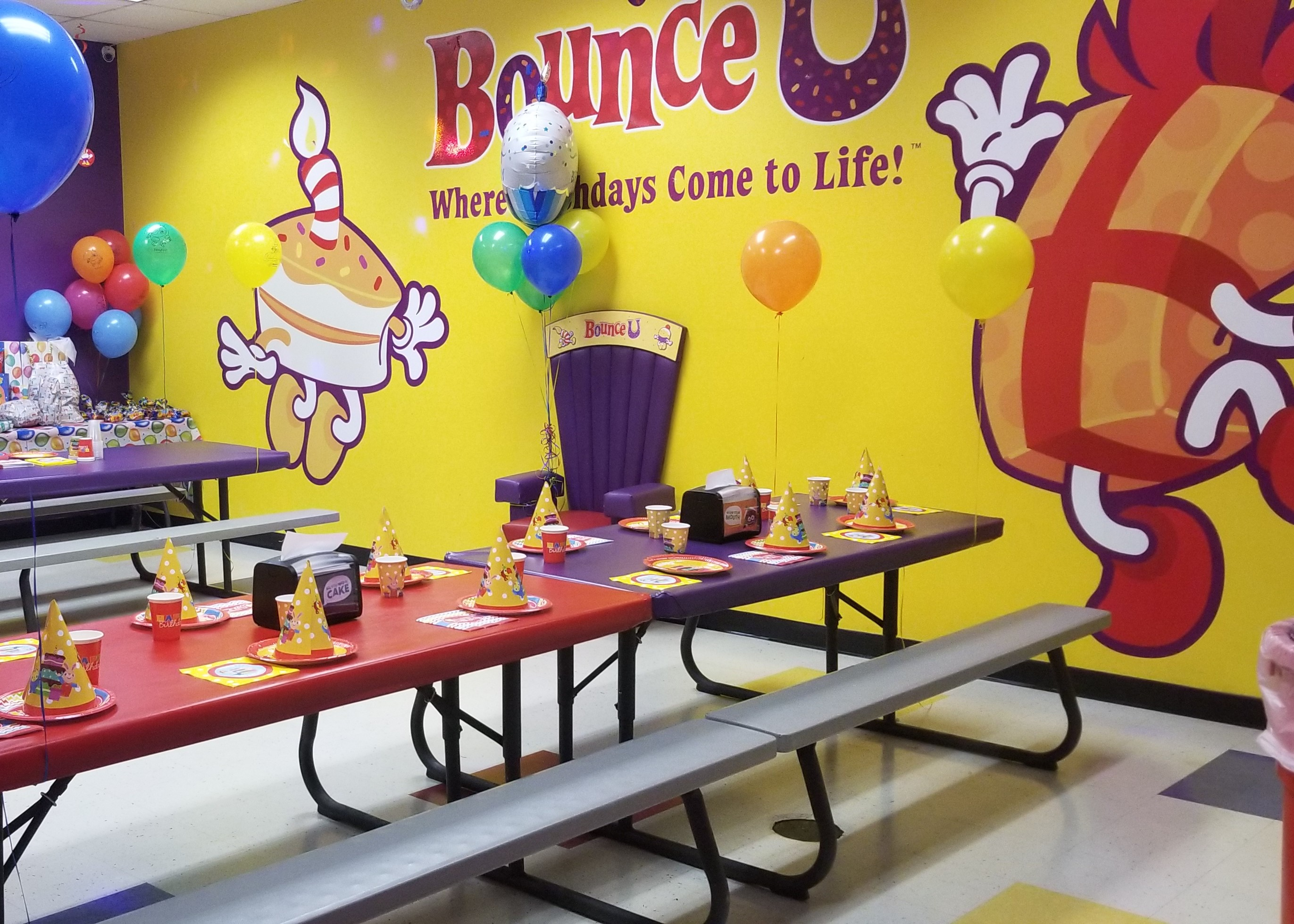 BounceU birthday party room with tables set up with plates and cups.