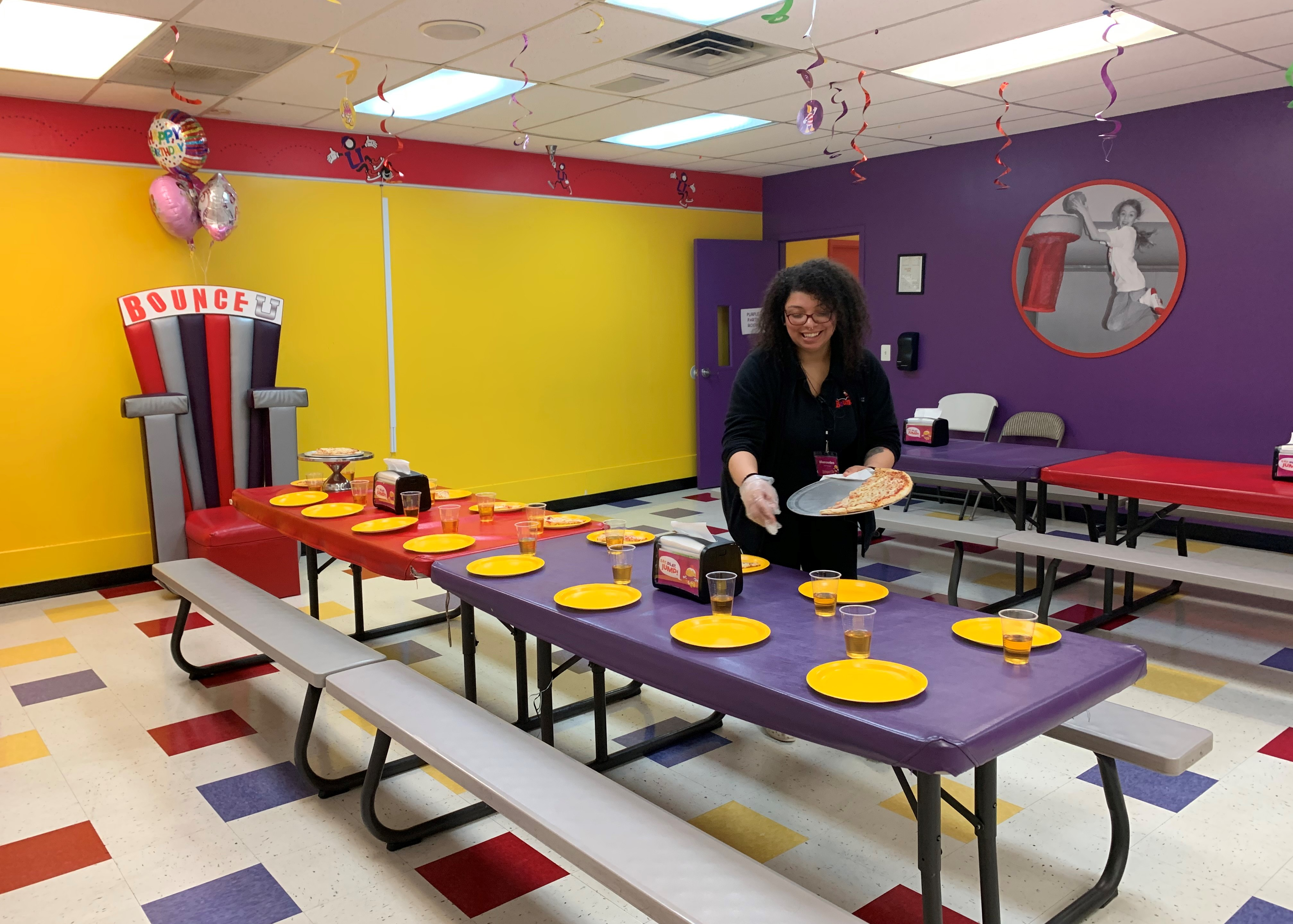 BounceU birthday party staff setting up plates and cups in a private party.