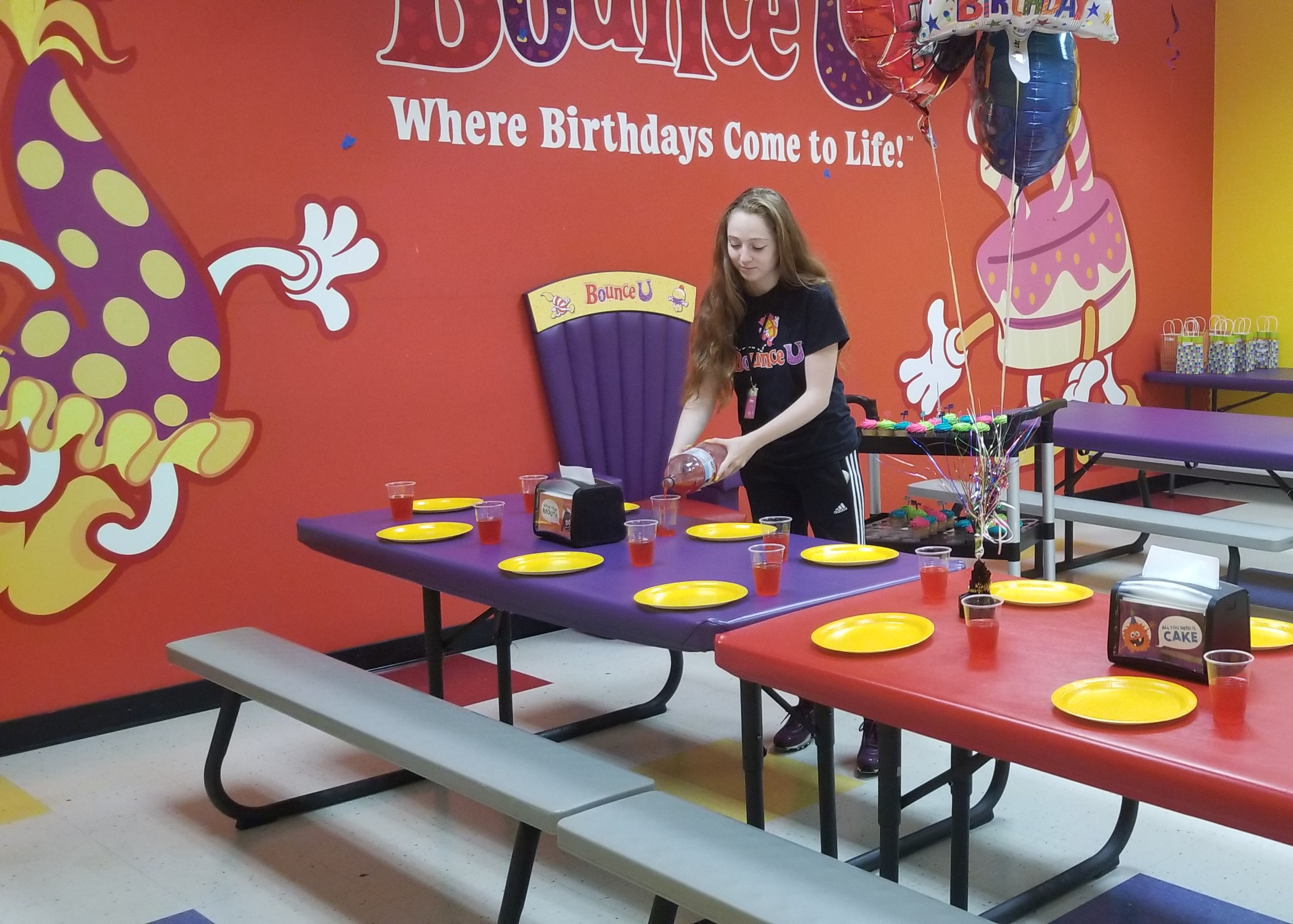 BounceU birthday party server pouring drinks in private party room.