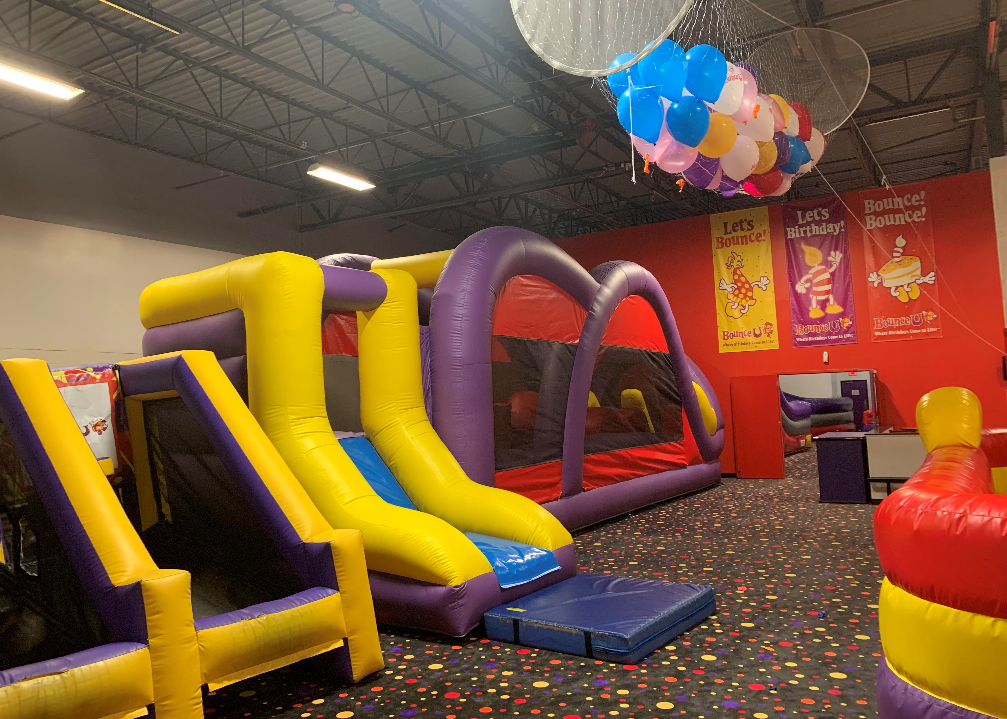 BounceU birthday party arena space with two large inflatable rides and a balloon drop filled with colorful balloons.
