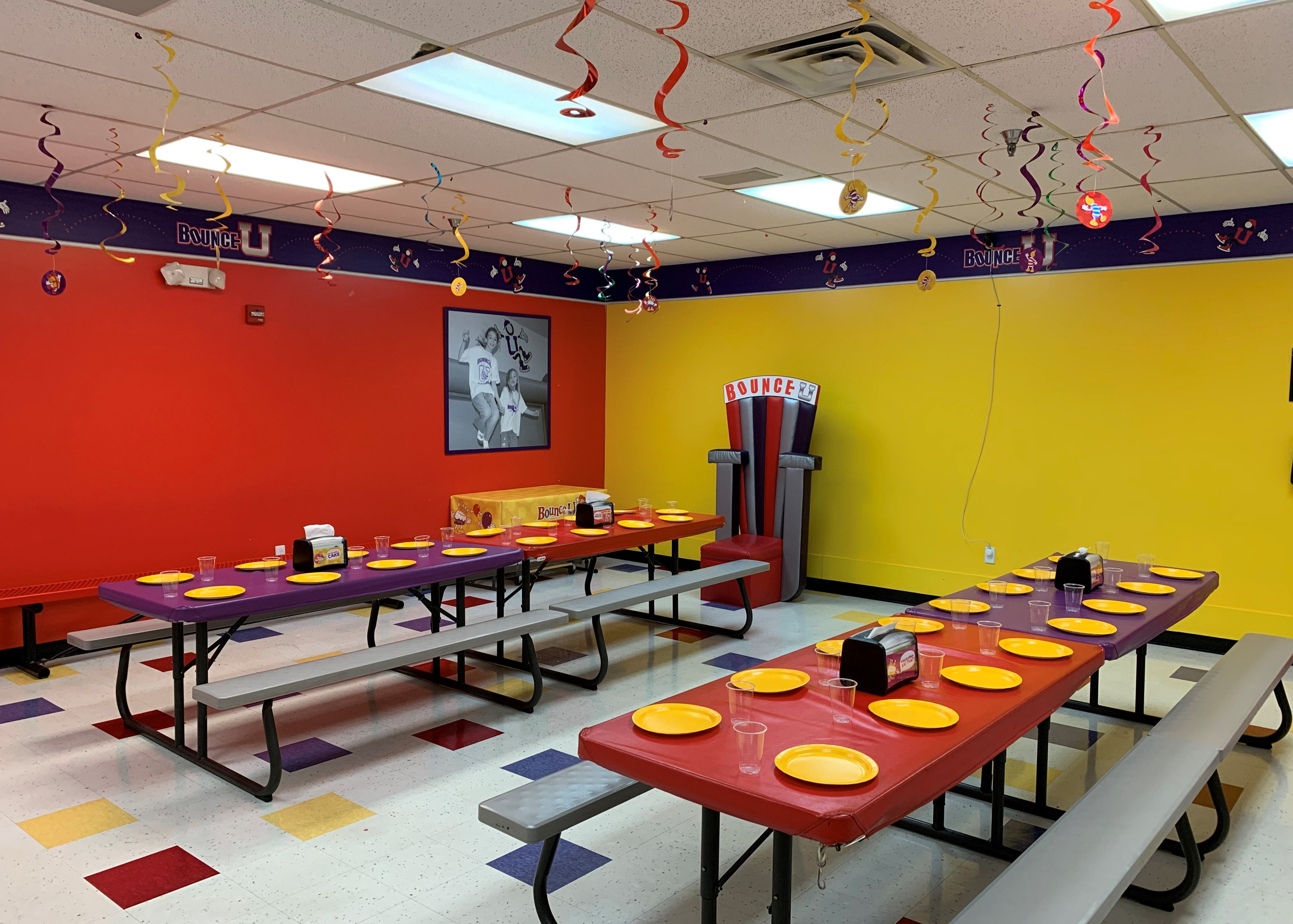BounceU birthday private party room with tables set up with plates and cups for kids.