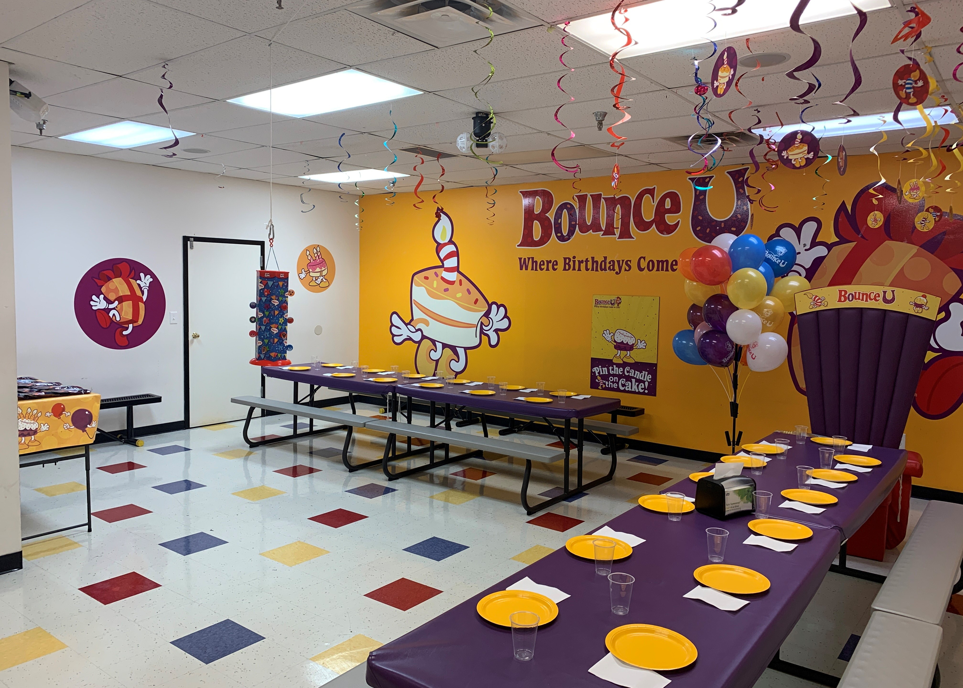 BounceU birthday party room with tables set up with plates and cups plus birthday throne for private parties.