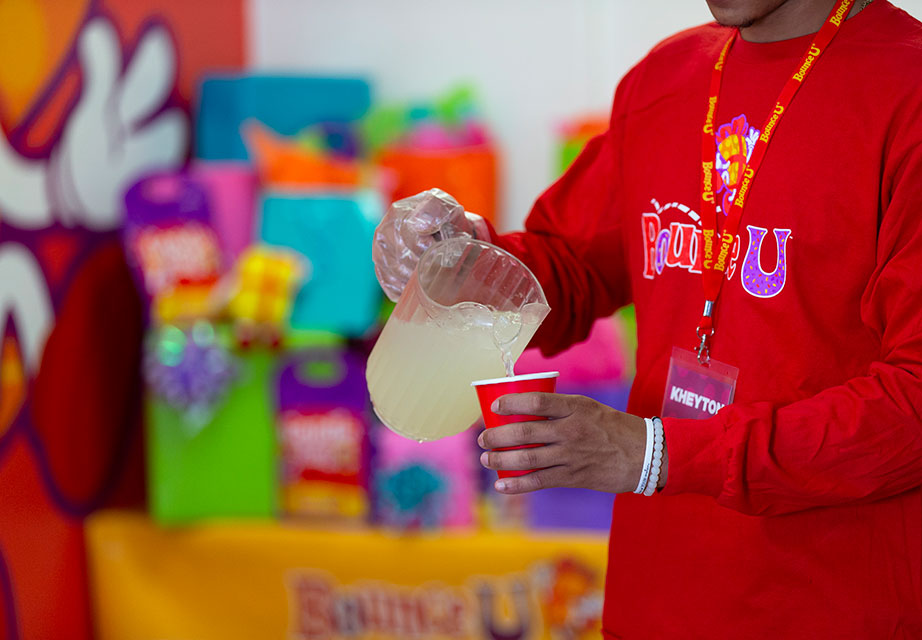 BounceU party server pouring kids drinks in private party room.