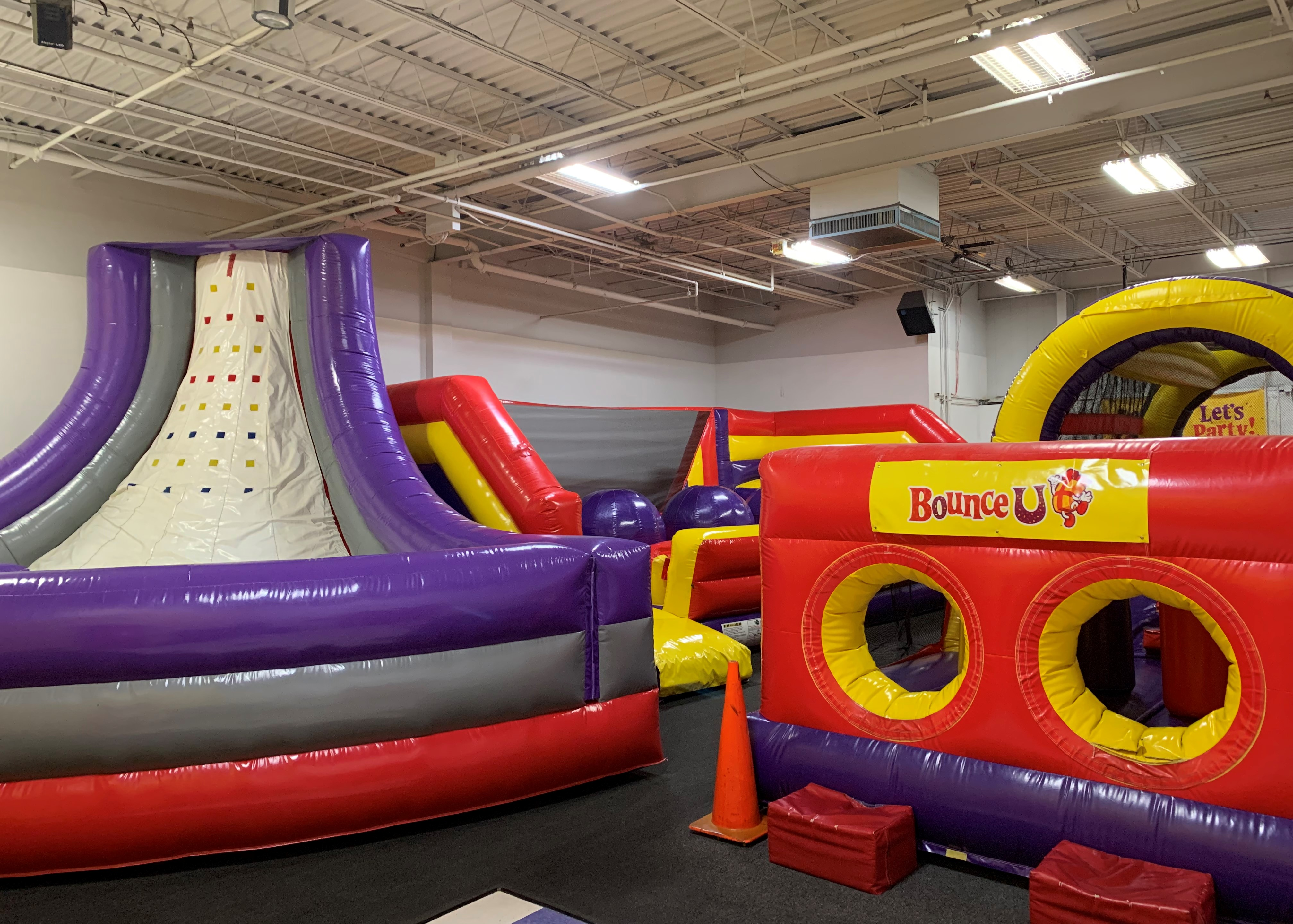 BounceU birthday party arena space with three large inflatable rides for private parties.