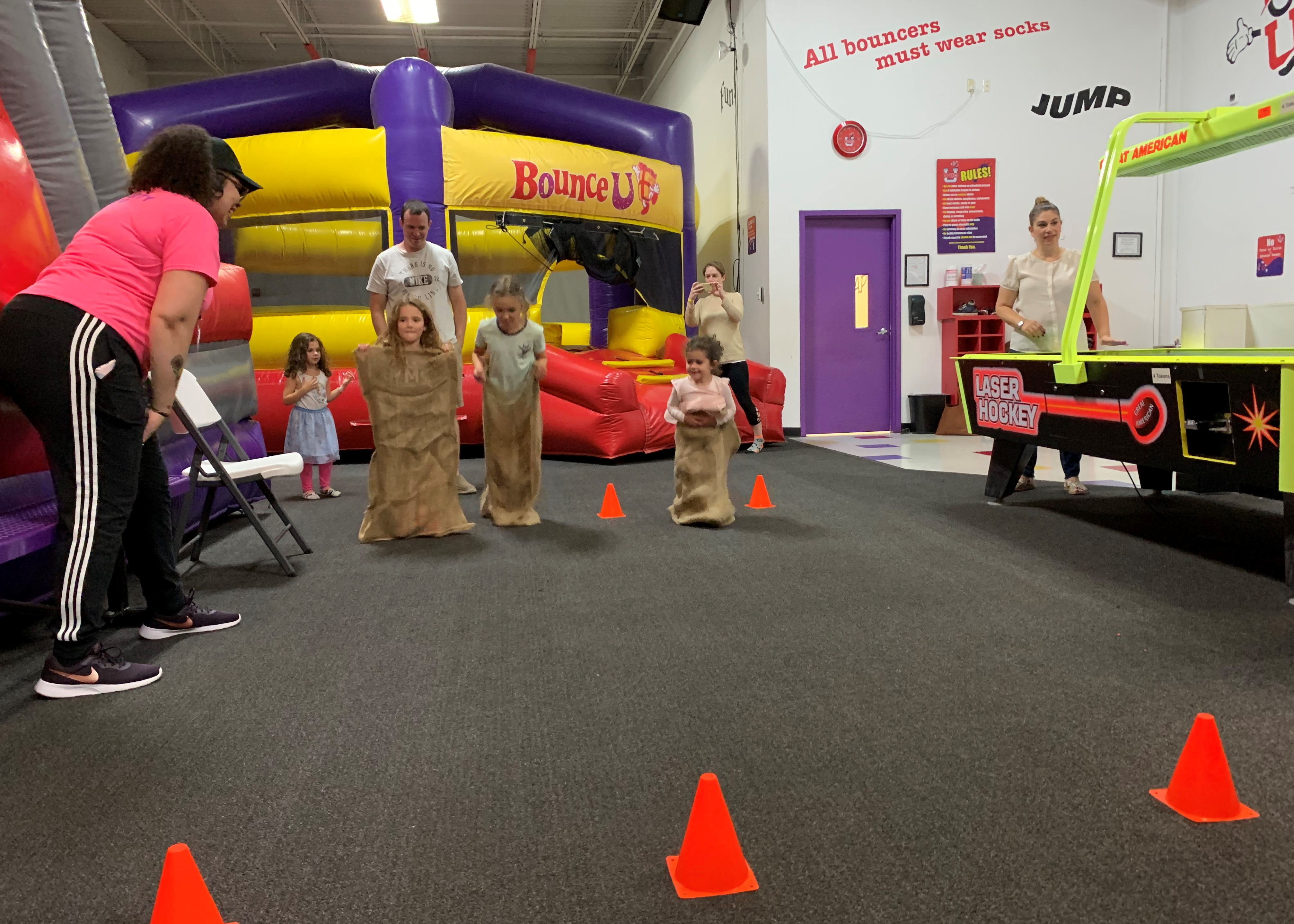 BounceU birthday party staff directing potato sack races with kids in a private party.